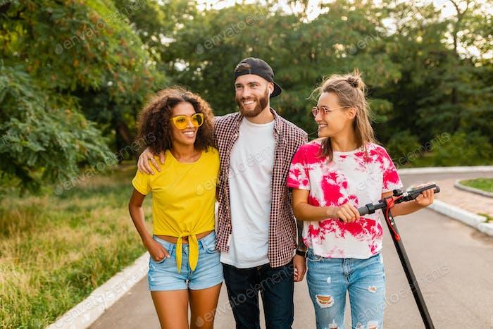 feliz joven compañía de amigos sonrientes caminando en el parque con patinete eléctrico