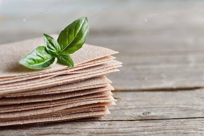 Raw lasagna sheets and basil leaves