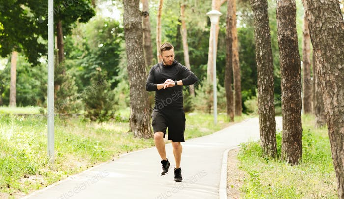 Millennial man jogging with fitness bracelet and checking his performance