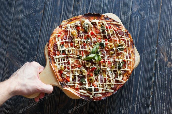 Hände liefern eine Pizza