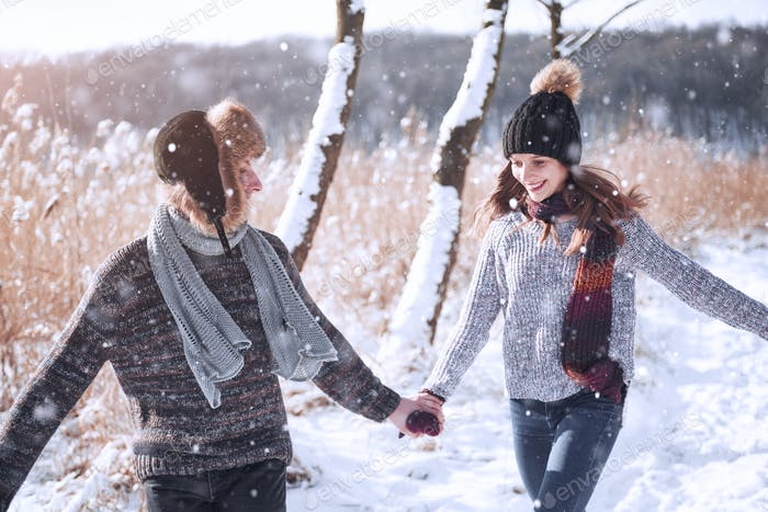 Young couple hugging each other in winter park. Winter love story, a beautiful stylish young couple