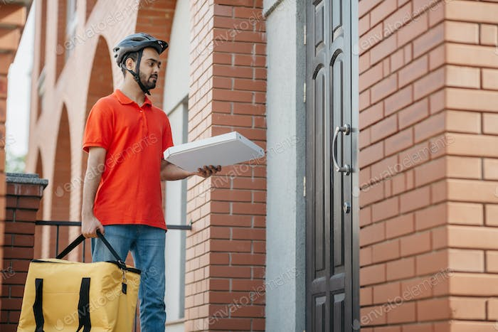 Courier delivers pizza to door. Young deliveryman with safety helmet holding large yellow bag and