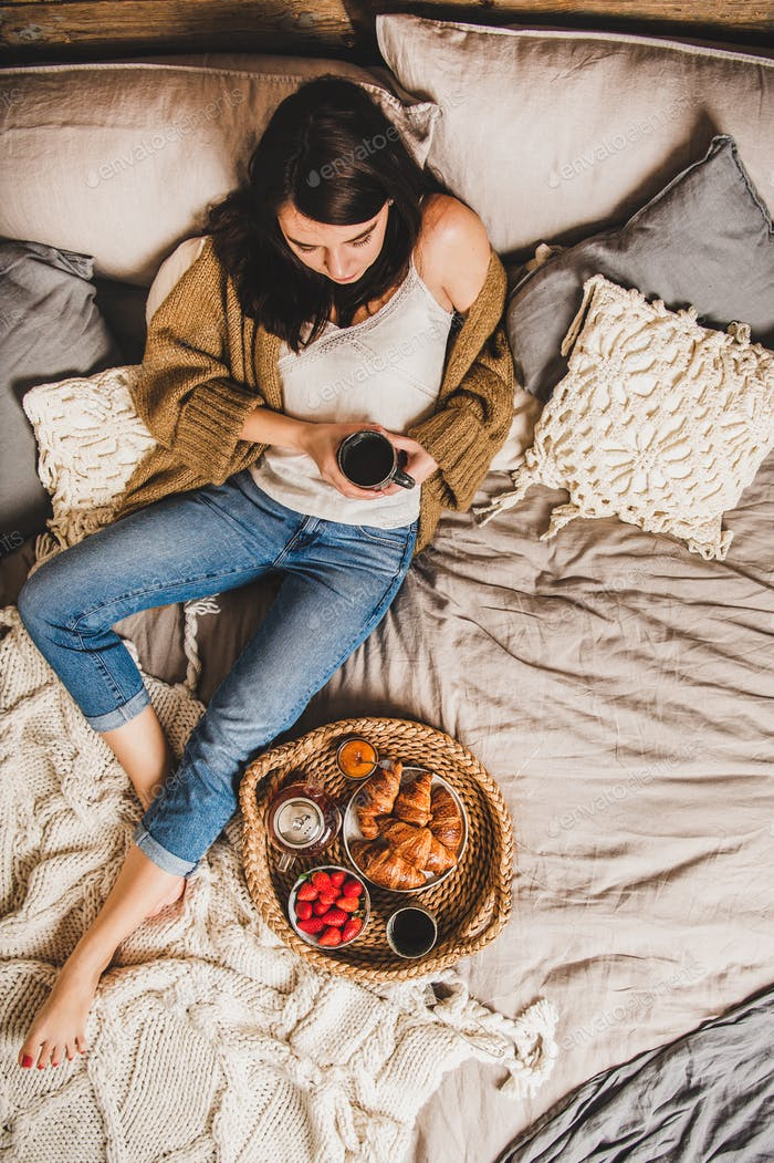 Young brunette woman sitting and having tasty breakfast in bed