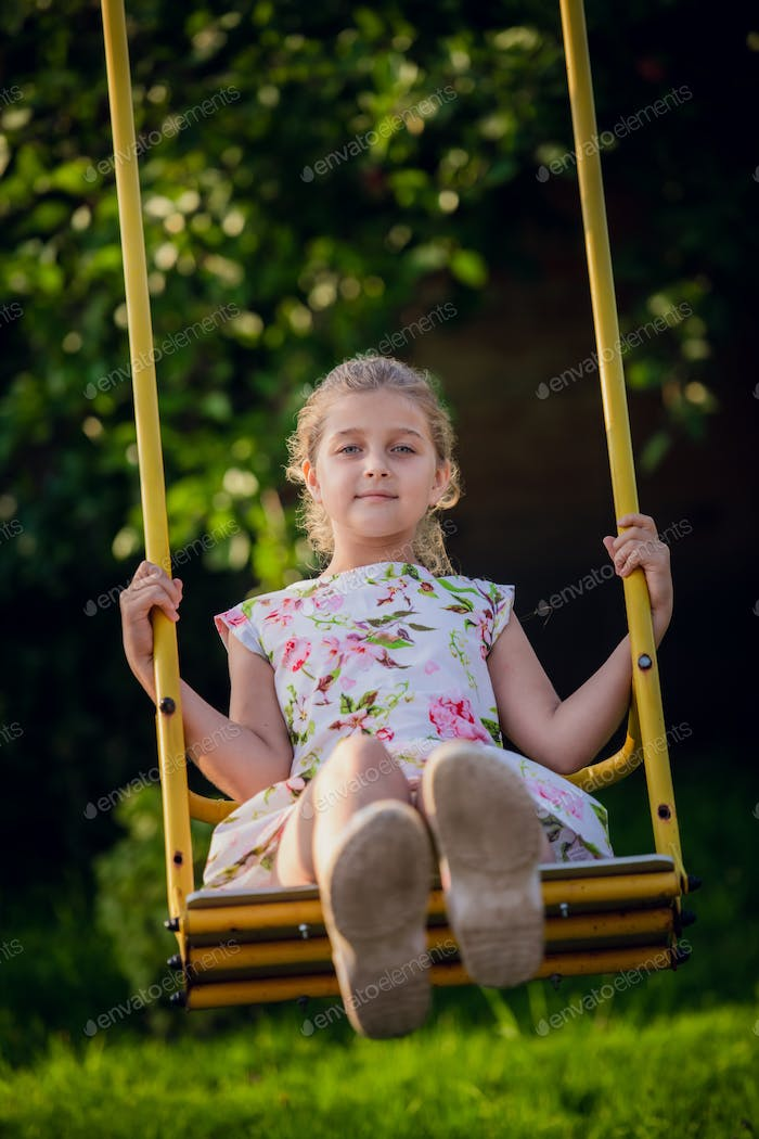 Adorable girl having fun on a swing on summer day