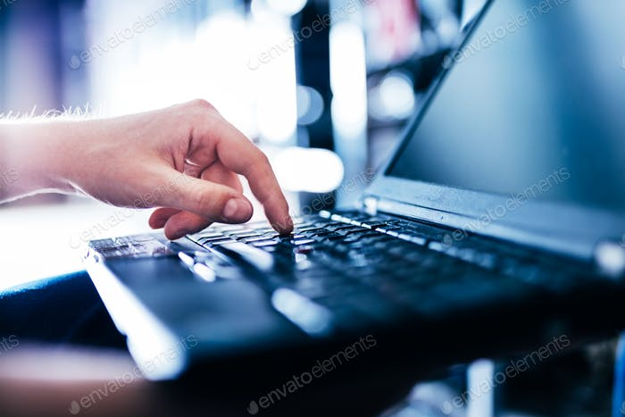 IT specialist pressing button on keyboard in big data center.