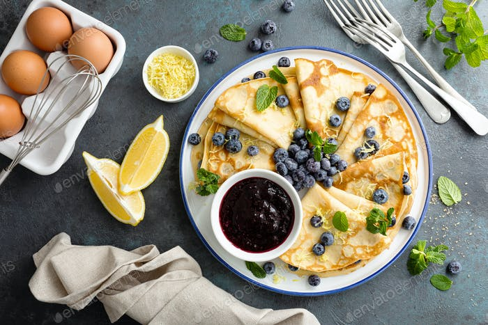 Crepes, thin pancakes with blueberry jam and fresh berries with lemon zest