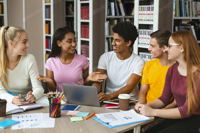 Friends discussing homework, studying at library together