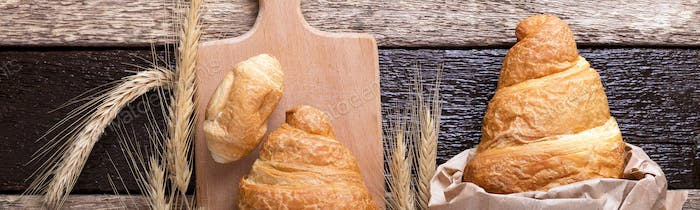 Banner of Croissants on board near wheat on wooden sackcloth background.