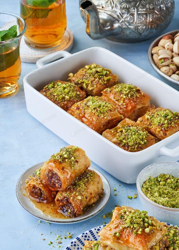 Middle eastern arab sweet pastry baklava with honey, pistachios, mint tea, selective focus. Ramadan.