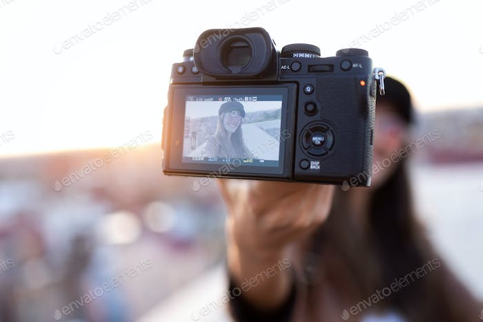 Pretty young woman taking a selfie with camera while sitting on the rooftop.