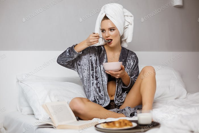 Cute lady in velvet robe sitting in bed with towel on head eating cereals thoughtfully looking aside