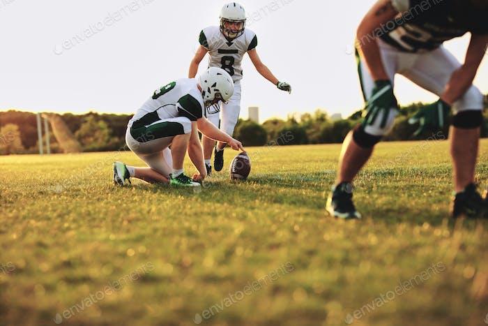 American Football-Spieler üben Platz treten während einer Teampraxis