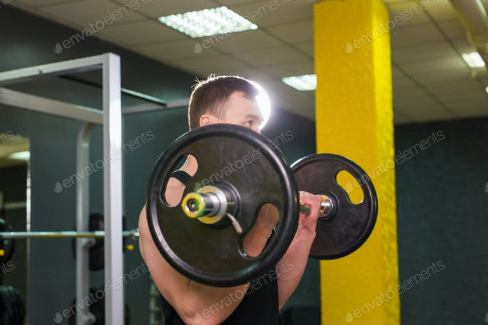 Muscular young man lifting weights in gym