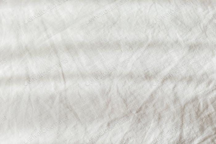 Closeup Textur aus weißem rauem Leinentextil mit Falten. Leerer Hintergrund