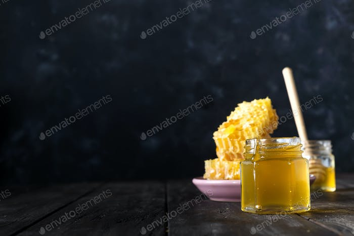 Delicious honey and fresh honeycombs on dark table with copy space