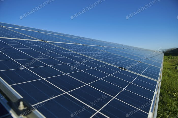Close up of a row of solar panels in an open field. A solar farm.