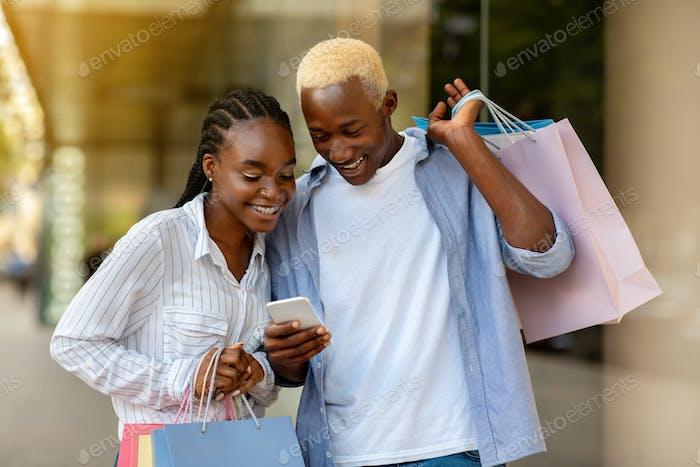 Werbung über den Verkauf auf dem Smartphone. Lächelnd Afroamerikaner Mann und Mädchen Blick auf Telefon