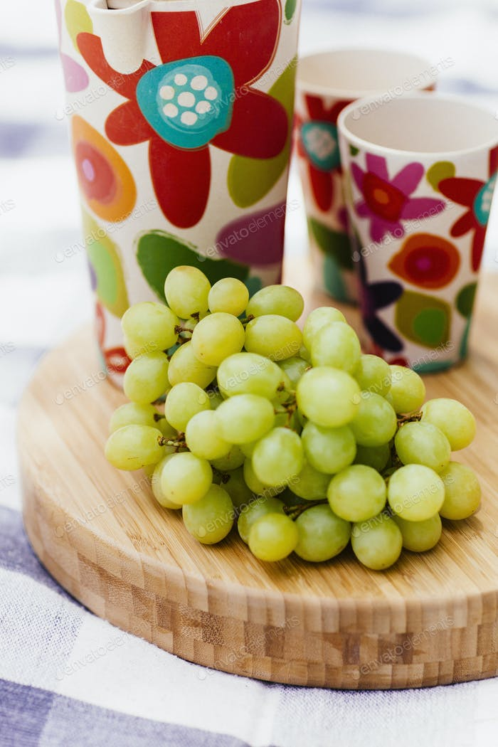 grapes and drinks on cutting board