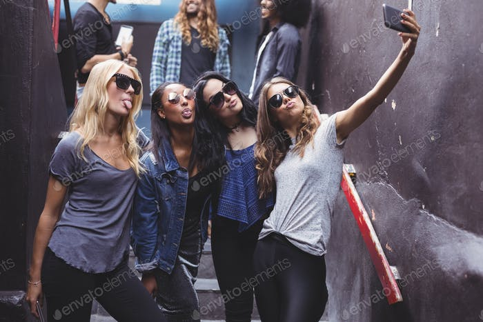 Female friends taking selfie while standing on steps