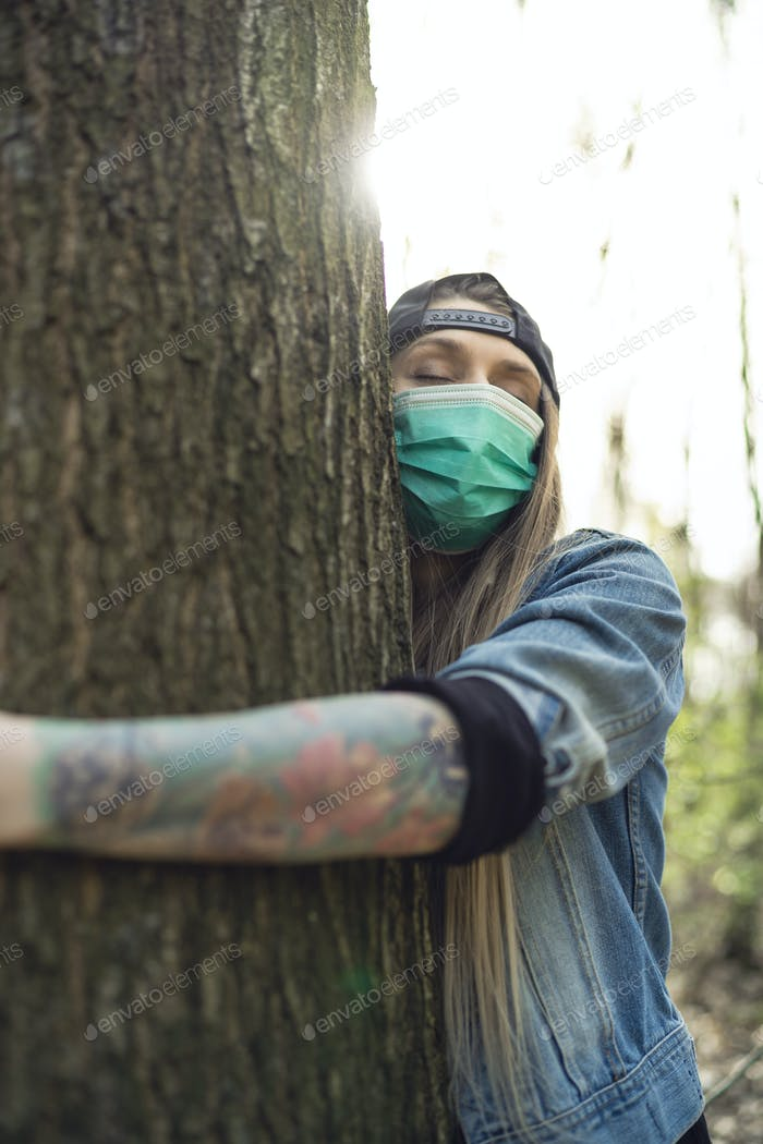 Casual Frau Umarging Baum in Park tragen Gesicht Schutz Maske gegen Coronavirus
