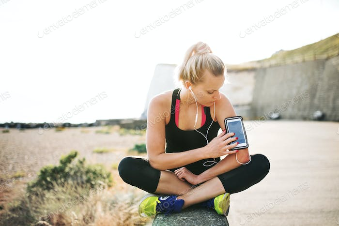 Young sporty woman runner sitting on the beach outside, using smartphone.