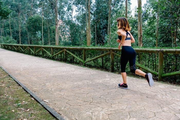 Woman running through a park