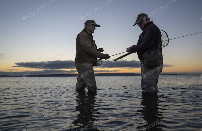 A male fly fisherman watches his guide work putting on a new fly to try for salmon or trout on  a