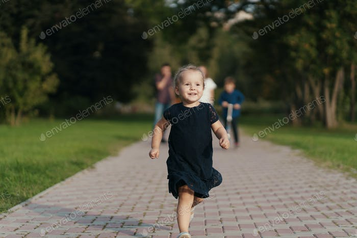 Little girl running while her family following her