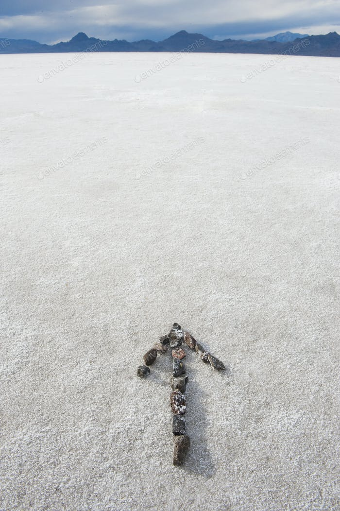 Pebbles arranged on salt flat in the shape of an arrow.