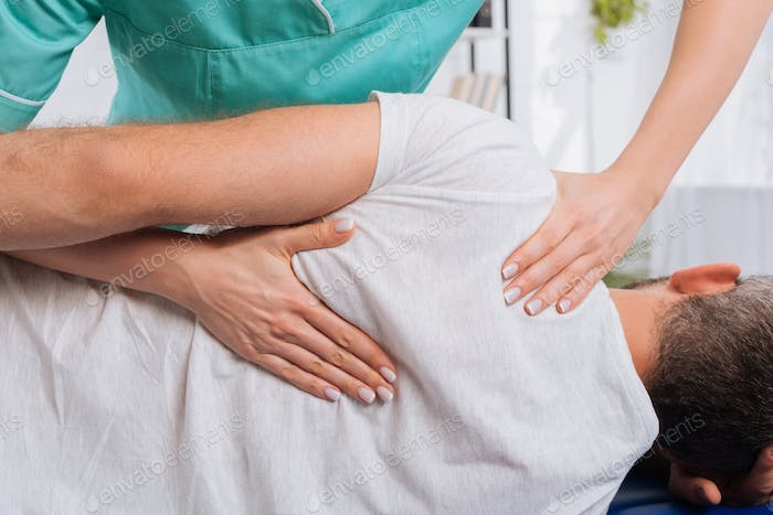 cropped shot of chiropractor massaging back on patient on massage table in hospital