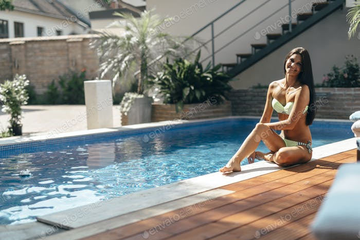 Beautiful woman by the pool enjoying summer
