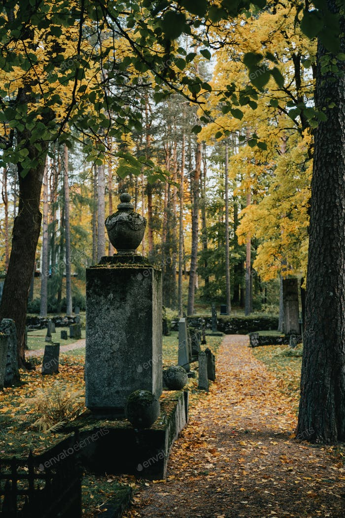 View of an old tombstone and path way across the cemetery at Autumn