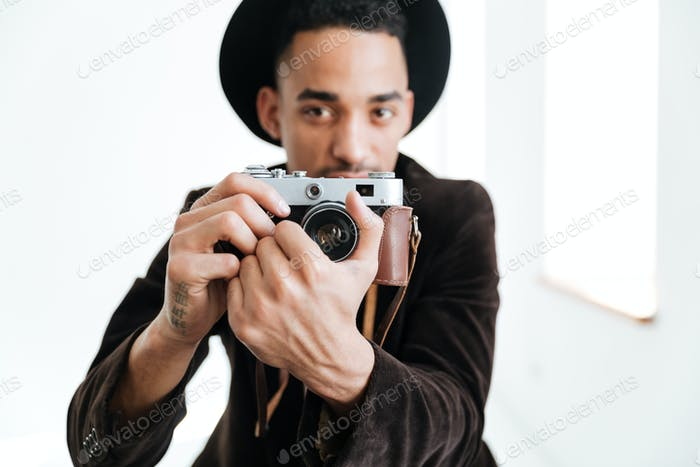 Young African man making photo on retro camera