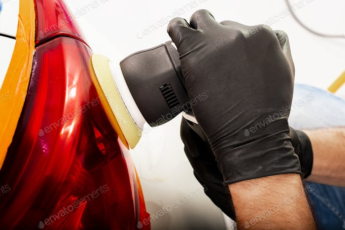 The man is polishing red back lights of a modern white car with polish machine