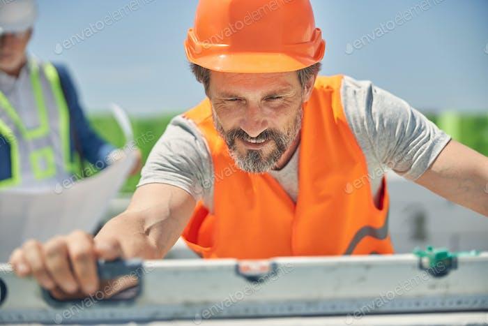 Two men in helmets focused on their work