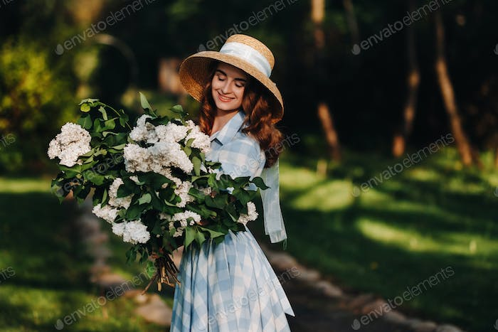 A stylish woman in a straw hat poses on lilac flowers in a Sunny spring Park. Calm portrait of a