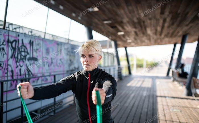 Eine junge Sportlerin mit elastischen Bändern, die im Freien in der Stadt trainieren.