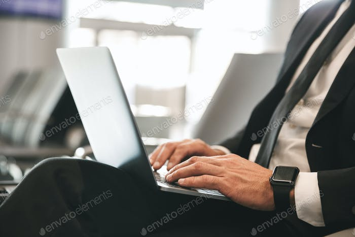 Close up of businessman dressed in suit using laptop