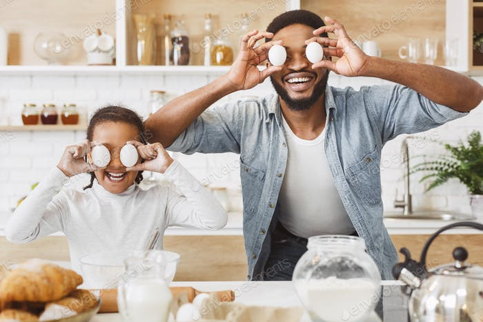 Funny father and daughter having fun while baking