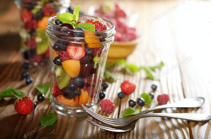 Assorted berries in mason jar on kitchen wooden table with fork
