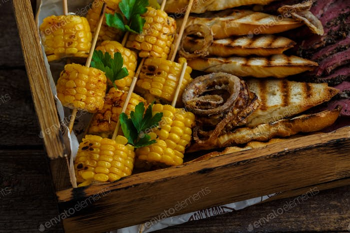 Close view of grilled corn and onion rings