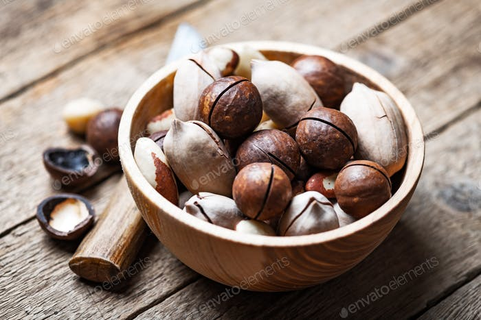 Dried mixed nuts in wooden bowl closeup
