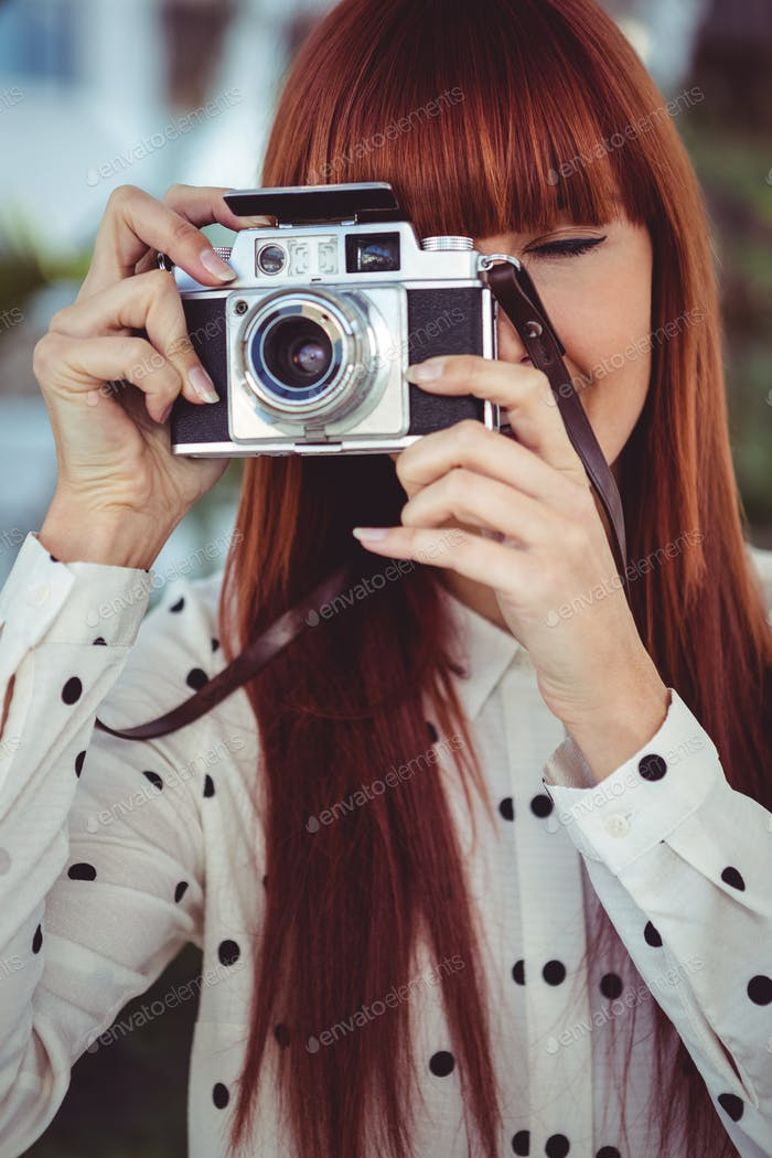 Attractive hipster woman using old fashioned camera in the garden