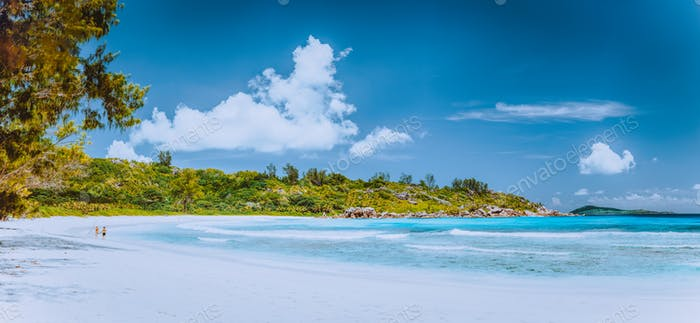 Panorama with couple walking on the picturesque white sand beach, Seychelles, La Digue, Anse Cocos