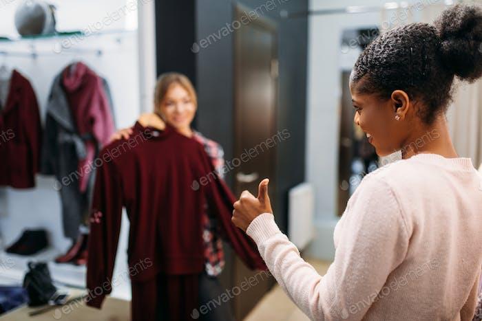 Zwei Frauen wählen Kleidung, Einkaufen