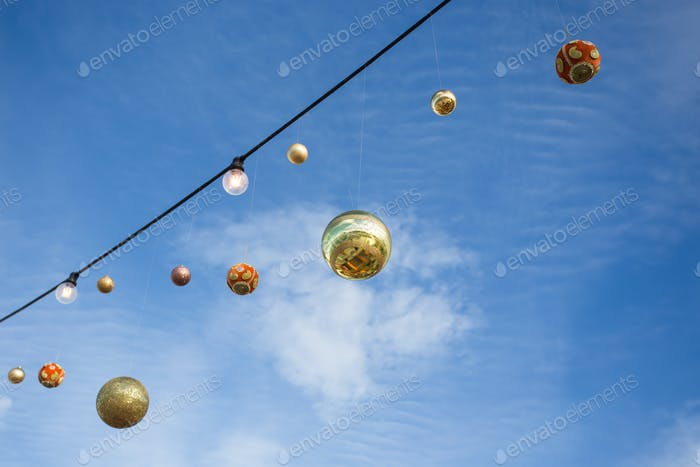 Christmas balls hanging against the blue sky