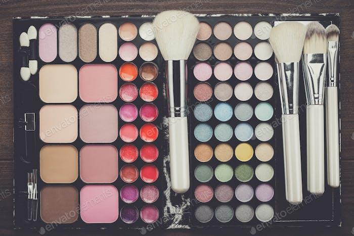 white make-up brushes on wooden background