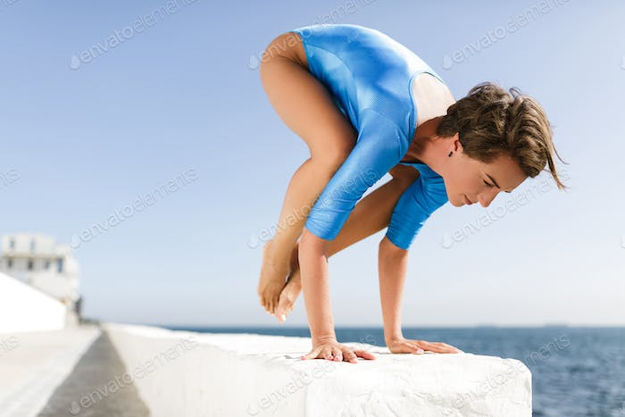 Woman with dark short hair in blue swimsuit practicing yoga poses while standing on her hands