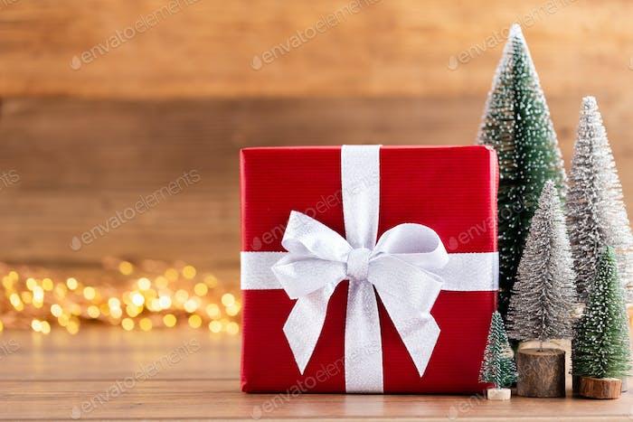 Weihnachtsgeschenk-Boxen mit Bändern und Baum auf Bokeh Hintergrund.