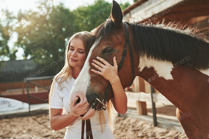 With eyes closed. Happy woman with her horse on the ranch at daytime